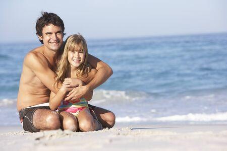 Father And Daughter Wearing Swimwear Sitting On Sandy Beach photo