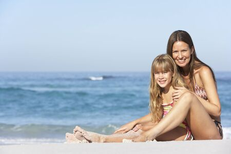 Mother And Daughter Relaxing Together On Beach Holiday photo