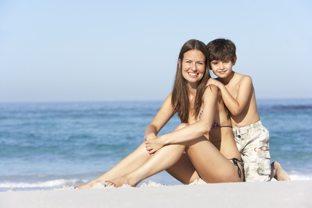 Mother And Son Relaxing Together On Beach Holiday photo