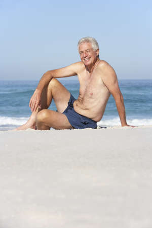 Senior Man On Holiday Sitting On Sandy Beach photo