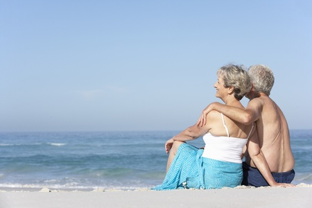 board shorts: Senior Couple On Holiday Sitting On Sandy Beach