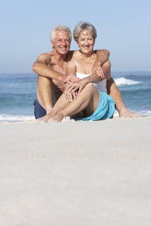 Senior Couple On Holiday Sitting On Sandy Beach photo