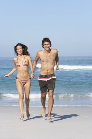 Young Couple Running On Beach Wearing Swimwear photo