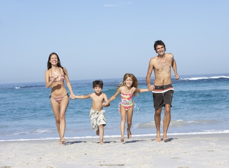 7 year old girl: Young Family Running Along Beach on Holiday Stock Photo