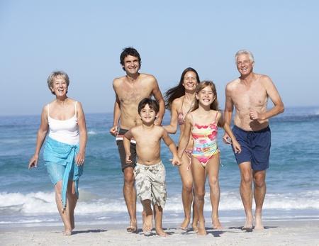 senioren wandelen: Drie-generatie familie op vakantie wandelen langs strand Stockfoto