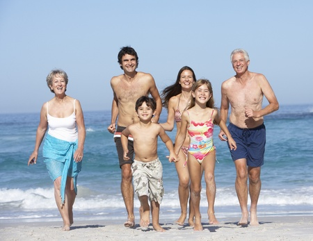 Three Generation Family On Holiday Walking Along Beach Stock Photo - 8482827