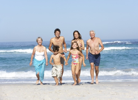 Three Generation Family On Holiday Walking Along Beach Stock Photo - 8482986