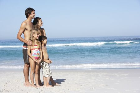 7 year old girl: Young Family Standing On Sandy Beach on Holiday