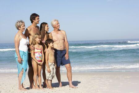 Three Generation Family On Holiday Walking Along Beach photo