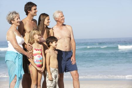 grandddaughter: Three Generation Family On Holiday Walking Along Beach