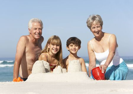 Grandparents And Grandchildren Building Sandcastles Together On Beach Holiday photo