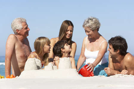 Three Generation Family Building Sandcastles On Beach Holiday photo