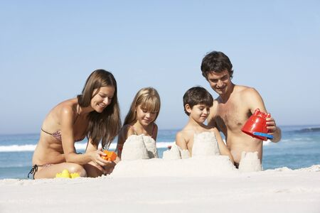 Family Building Sandcastles On Beach Holiday photo