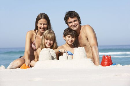 Family Building Sandcastles On Beach Holiday Stock Photo - 8483061