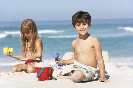 enfant maillot: Renforcement des enfants ch�teaux de sable sur la plage Holiday