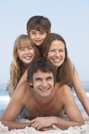 board shorts: Young Family Having Fun On Beach Holiday