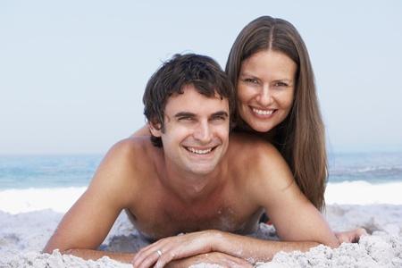 Young Couple Relaxing On Beach Wearing Swimwear photo