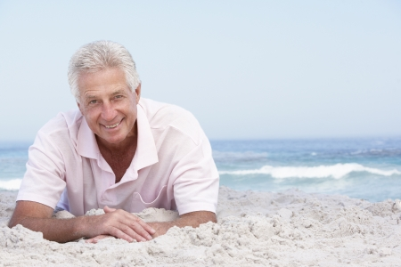 Senior Man Relaxing On Sandy Beach photo