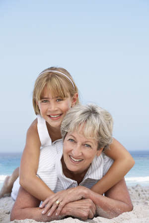 Grandmother Relaxing On Sandy Beach With Granddaughter Stock Photo - 8482898