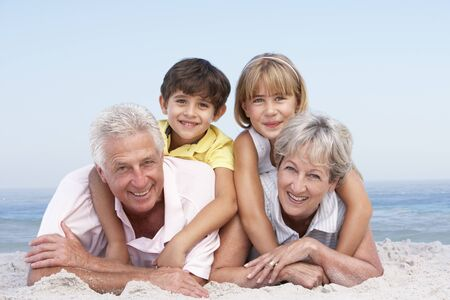 Grandparents And Grandchildren Relaxing On Beach Holiday photo