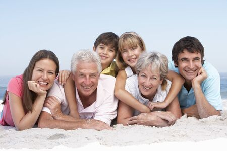 Three Generation Family Relaxing On Beach Holiday photo
