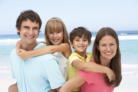 Family Having Piggyback Fun On Beach Holiday photo