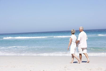 Senior Couple On Holiday Running Along Sandy Beach Stock Photo - 8482897
