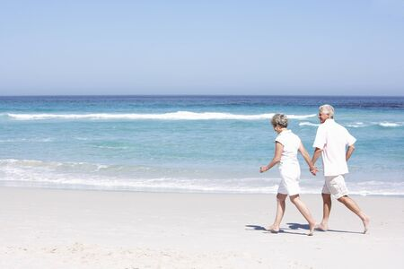Senior Couple On Holiday Running Along Sandy Beach photo