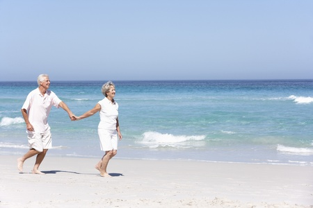 Senior Couple On Holiday Running Along Sandy Beach photo