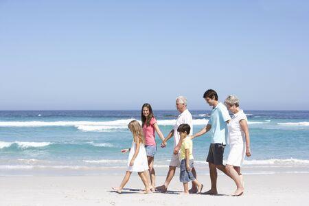 senioren wandelen: Drie-generatie familie wandelen langs zand strand
