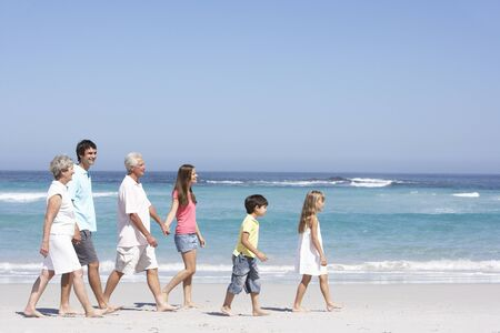 Three Generation Family Walking Along Sandy Beach photo