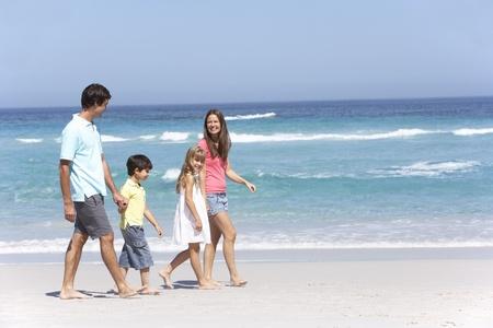 ni�os caminando: Familia caminando a lo largo de la playa de Sandy Foto de archivo