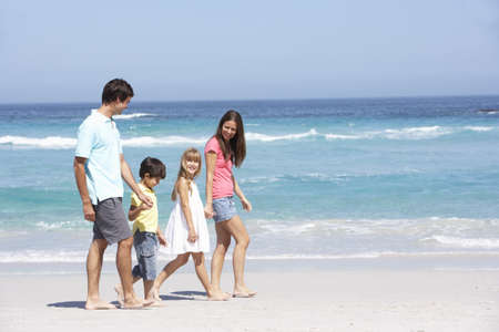 Family Walking Along Sandy Beach photo
