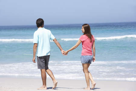 Couple On Holiday Walking Along Sandy Beach photo