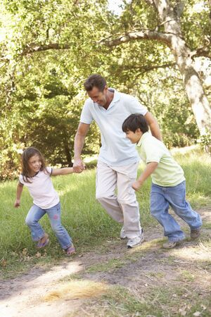 Father And Children Enjoying Walk In Park photo