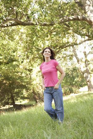 Young Woman Walking Through Long Grass In Park photo