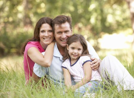 Family Sitting In Long Grass In Park Stock Photo - 8483230
