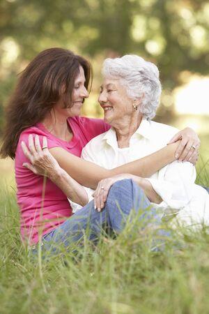 familia abrazo: Mujer senior con la hija de adulta en el Parque Foto de archivo