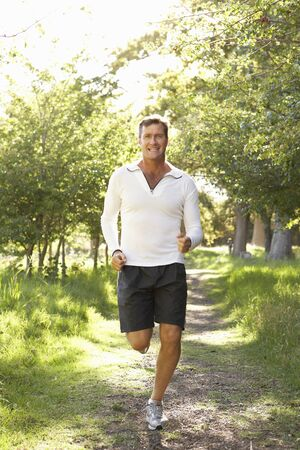 Middle Aged Man Jogging In Park photo