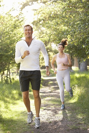 couple exercising: Middle Aged Couple Jogging In Park