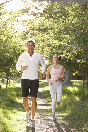 Middle Aged Couple Jogging In Park photo