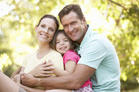 family in park: Family Sitting On Tree In Park Stock Photo