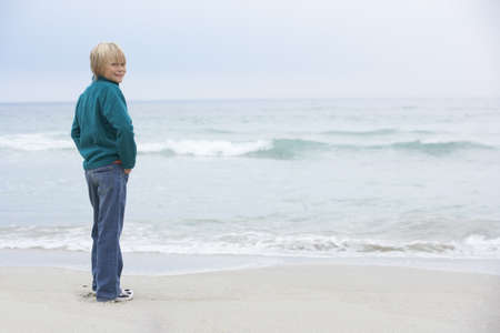 Young Boy On Holiday Standing On Winter Beach Looking Out To Sea Stock Photo - 8483021