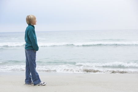 Young Boy On Holiday Standing On Winter Beach Looking Out To Sea Stock Photo - 8482980