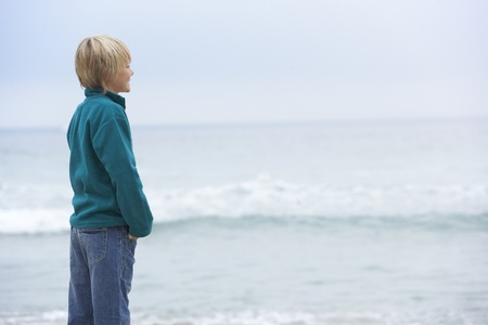 Young Boy On Holiday Standing On Winter Beach Looking Out To Sea Stock Photo - 8482946