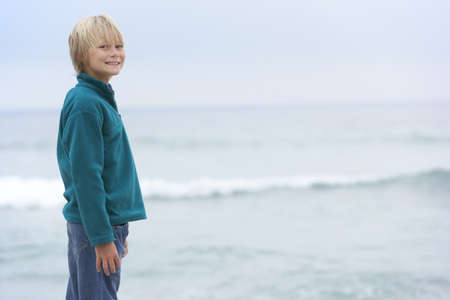 Young Boy On Holiday Standing On Winter Beach Looking Out To Sea Stock Photo - 8482999