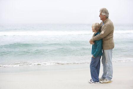 abuelo: Abuelo y son permanente juntos en la playa de invierno Foto de archivo