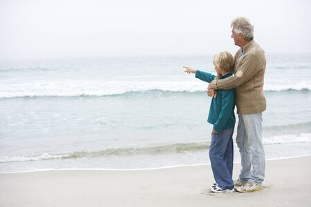 Grandfather And Son Standing On Winter Beach Together photo