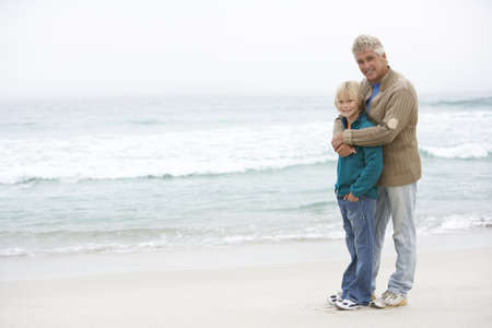causal clothing: Grandfather And Son Standing On Winter Beach Together Stock Photo