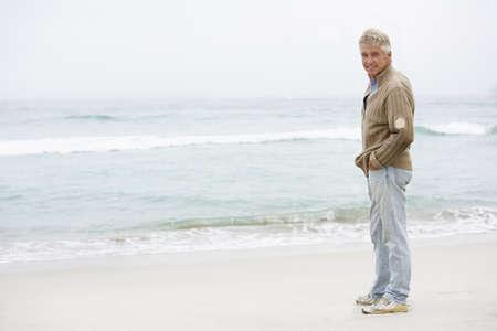 Senior Man On Holiday Standing On Winter Beach Stock Photo - 8482895